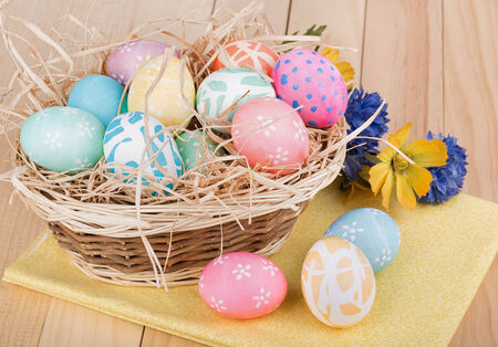 Decorated Easter eggs in and in front of a basket