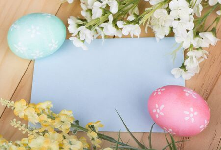 Easter eggs and flowers around a blank card