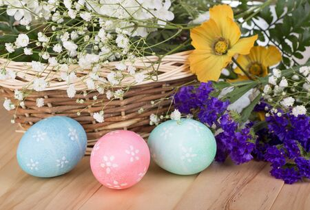 Three colored Easter eggs with flowers and basket