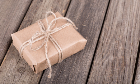 Gift wrapped in brown paper and string on an old wood surface