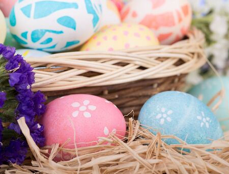 Closeup of two colored Easter eggs with a basket of eggs in back