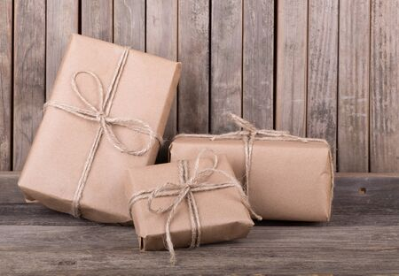 Three packages wrapped in brown paper and string on old wood deck