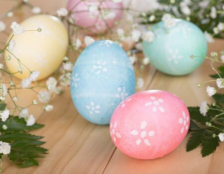 Group of colored Easter eggs among white flowers