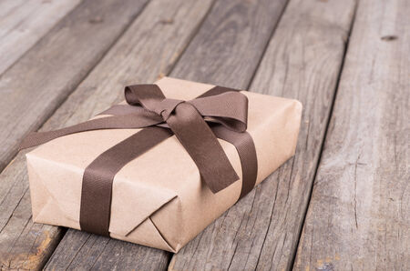 Package wrapped in brown paper, ribbon and bow on a wooden board background