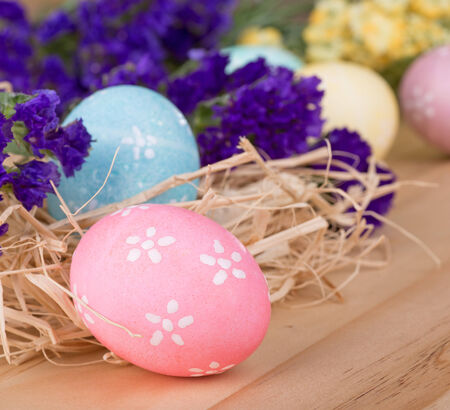 Decorated Easter eggs among flowers on a wood surface Banco de Imagens