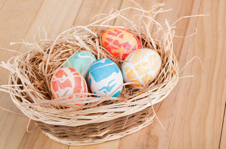 Basket of colored easter eggs on a wood surface Banco de Imagens