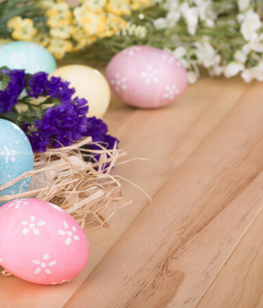 Colorful easter eggs and flowers on a wood surface Banco de Imagens