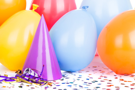 Birthday party hat and balloons with confetti and a noisemaker Banco de Imagens