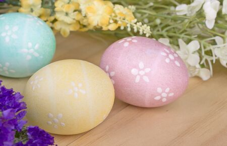 Three colored Easter eggs and flowers on a wood surface Banco de Imagens