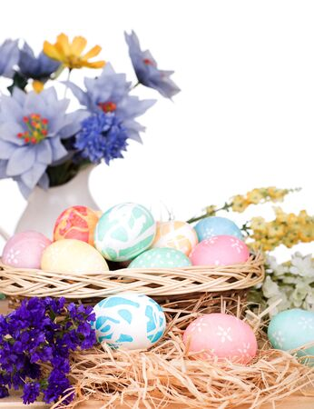 Bunch of Easter eggs in and around a basket on a white background