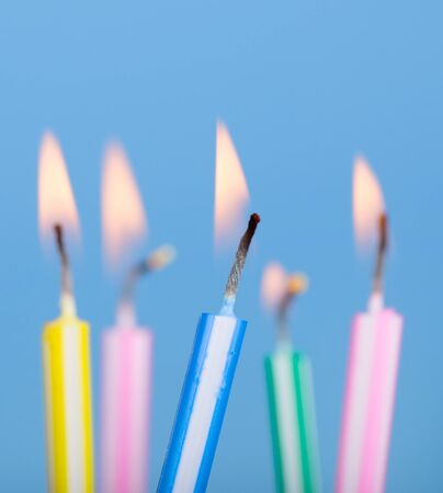 festive occasions: Burning birthday candles on a blue background Stock Photo