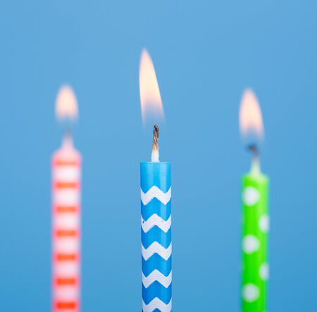 Three burning birthday candles on a blue background