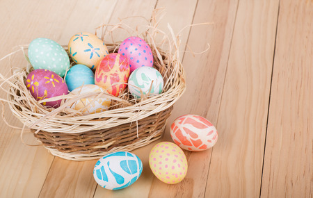 Colored Easter eggs with a basket on a wooden surface Banco de Imagens