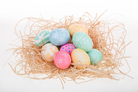 Decorated Easter eggs on top of raffia on a white background Banco de Imagens