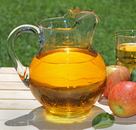Pitcher of apple juice with apples on a wooden table