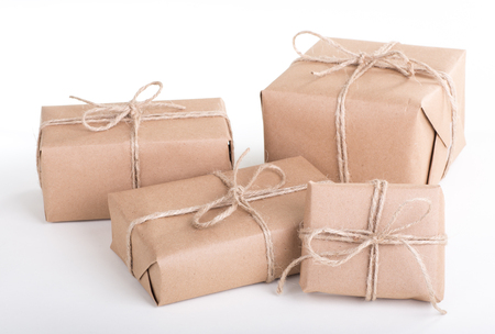Several packages wrapped in brown paper tied with string on a white background