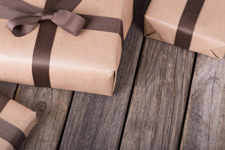 Gifts wrapped in brown paper and ribbon on old wood boards