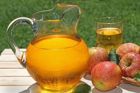 Pitcher of apple juice and apples on a table