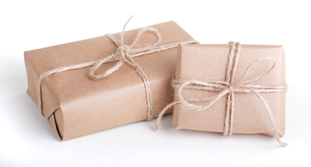 Two packages wrapped in brown paper tied with string on a white background Banco de Imagens