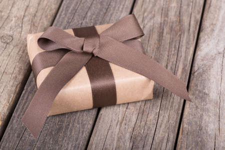 Small gift wrapped in brown paper, ribbon and bow on old wood boards