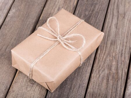 Package wrapped in brown paper and string on old wooden planks