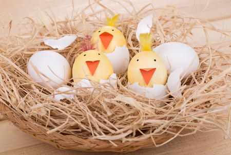 Decorated Easter eggs to look like hatching chicks in a basket