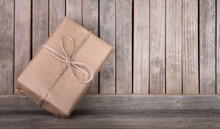 Package wrapped in brown paper and string leaning against a wood fence Banco de Imagens