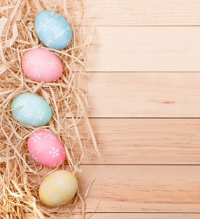 pastel colour: Vertical Easter egg border on a wood background