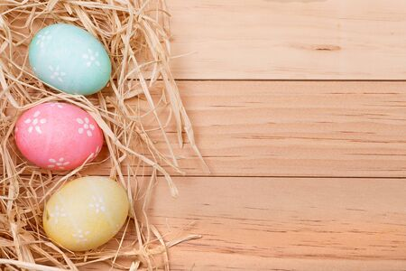Three decorated Easter eggs on a wood background for copy space