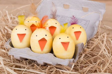 Decorated Easter eggs to look like chicks in an egg carton