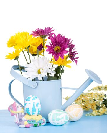 Easter eggs and flowers in a watering can on a white background