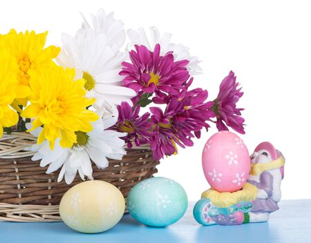 Decorated Easter eggs and basket of flowers on a white background Banco de Imagens