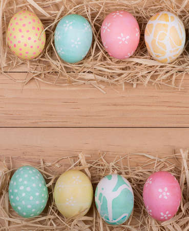 Border of Easter eggs on wood background