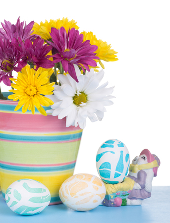 Flower pot with flowers and Easter eggs on a white background Banco de Imagens