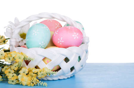Decorated Easter eggs in a basket on a white background