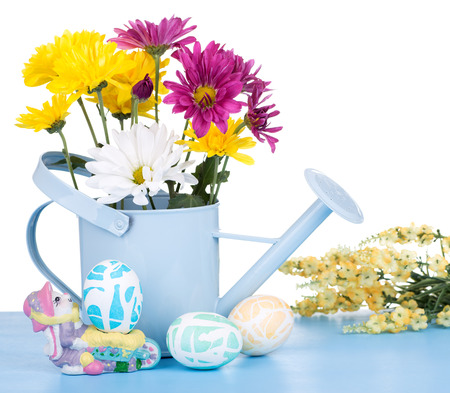 Watering can with flowers and colored easter eggs on a white background Banco de Imagens