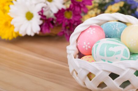 Decorated Easter eggs in a basket with flowers in background