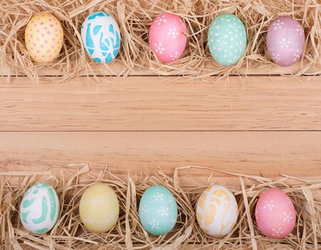 Decorated Easter eggs forming a border on a wood background