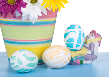 Three decorated Easter eggs with flowers in a pot on a white background Banco de Imagens