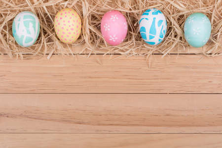 Border of Easter eggs and raffia on wood background Banco de Imagens