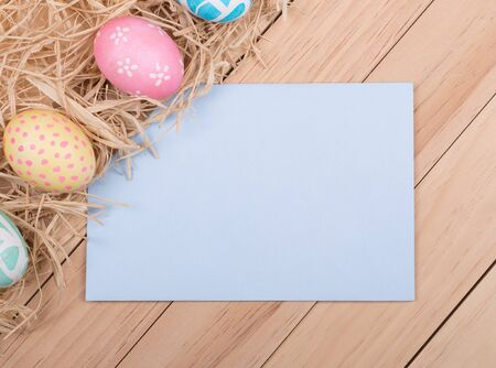 Decorated Easter eggs next to envelope on a wood background