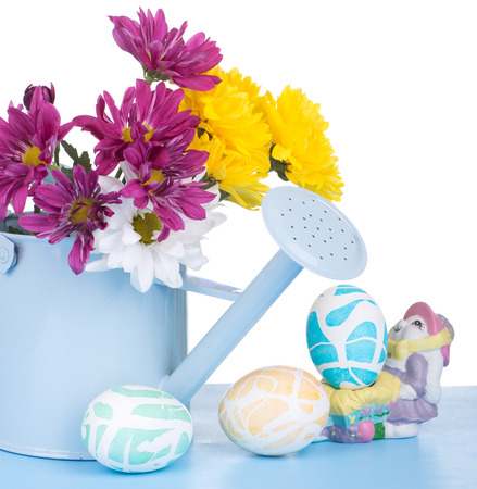 Colored Easter eggs and a watering can of flowers on a white background