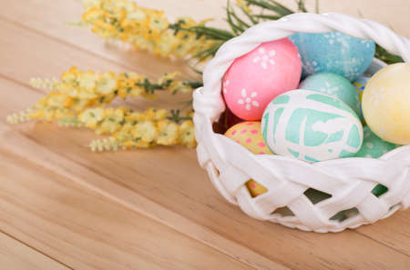 Decorated Easter eggs in a white basket on a wood surface Banco de Imagens