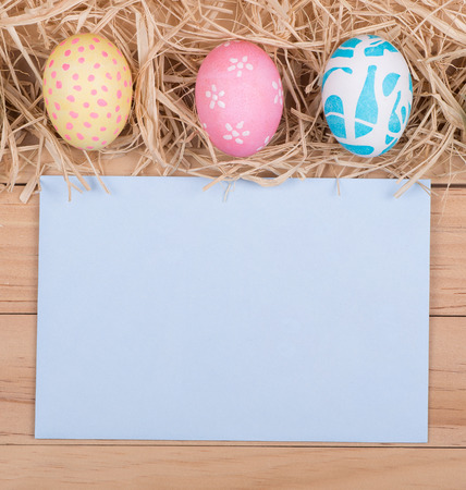 bordering: Three colored Easter eggs bordering a blank envelope Stock Photo