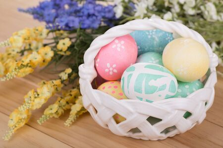 Decorated Easter eggs in a basket with flowers Banco de Imagens