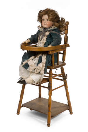 high chair: Large German ceramic doll impressed A.m. jointed and dressed in velvet in a child high chair.