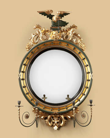 convex: old antique round convex gilded hall mirror with eagle and candle holders. 18 - 19th century Stock Photo