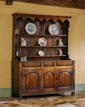 antique: old antique hand made and oak carved English wooden kitchen dresser Stock Photo