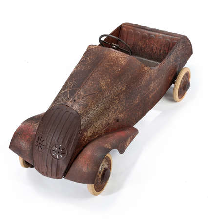 Old childs toy pedal car well used now rusty on a white background photo