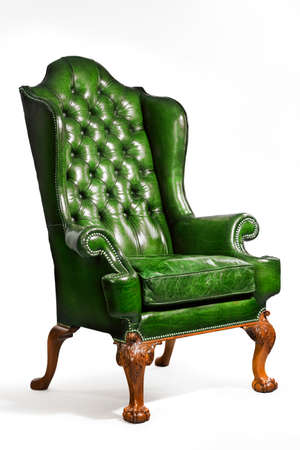 antique chair: old comfortable antique green leather wing arm chair 18 - 19th century Stock Photo
